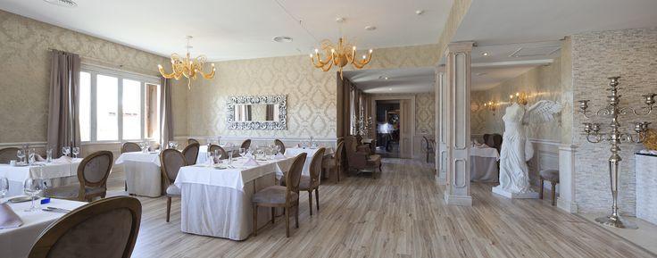 Comedor del restaurante italiano. La elegancia del contraste entre la tarima de madera clarita y el dorado de las lámparas es perfecta.