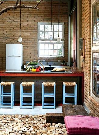 O balcão da cozinha, em Campos do Jordão (SP), foi revestido com tacos de ipê e é o único elemento que a separa de uma área da sala, onde o piso de tijolo é interrompido por uma forração de pedra madeira, uma alternativa aos pedriscos