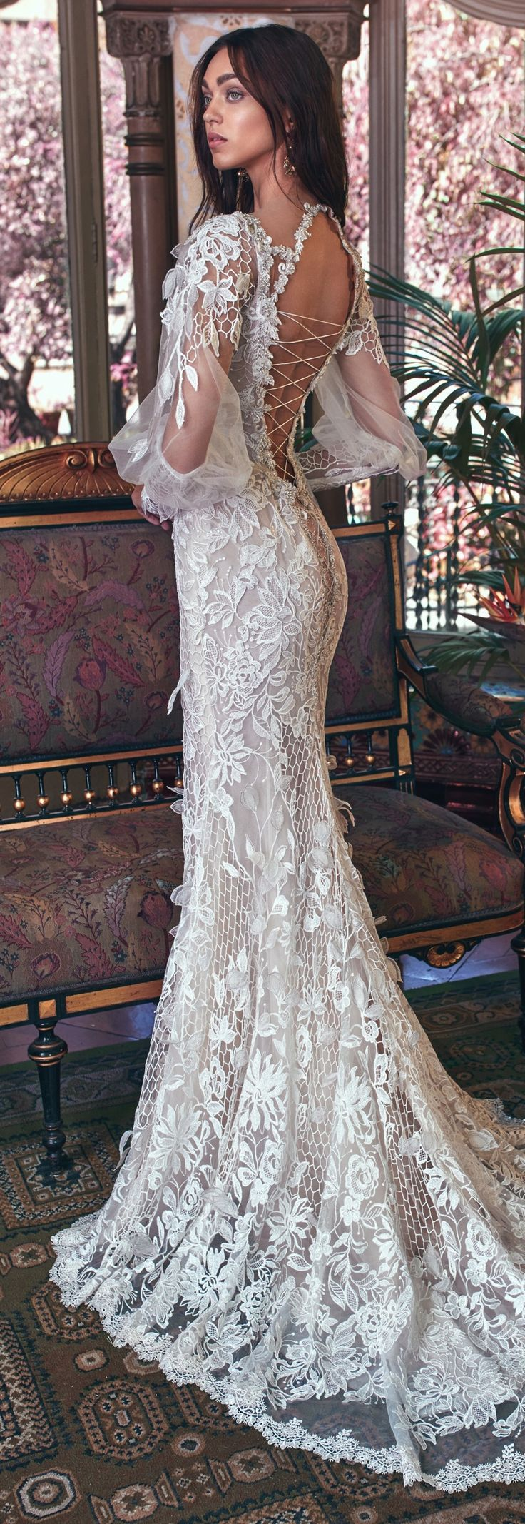 A sheer 3D lace gown with open work fish net elements, a low plunging V neckline, and sheer Victorian sleeves with lace cuffs. The gown has a light powder pink background and the lace is embroidered with silver thread. The neckline is embroidered with an antique Victorian embroidery. The back has a very low V and is laced all the way down.