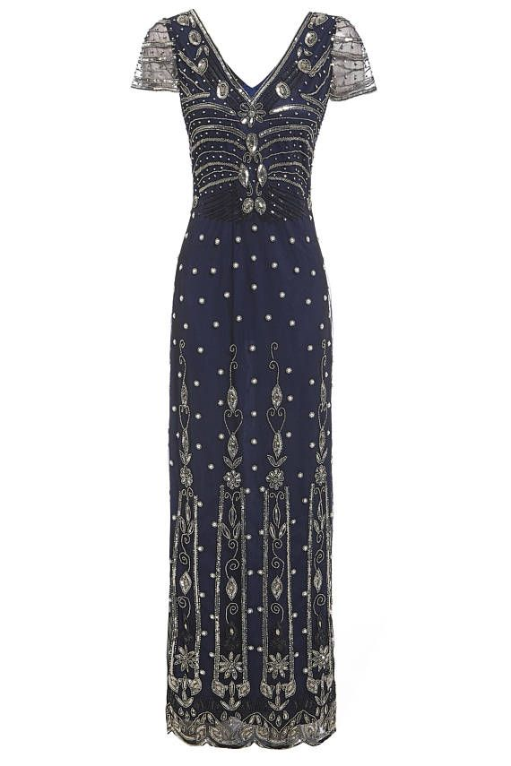 871bc59b05de Elegant long evening embellished gown boasting intricate silver bead and  sequin detailing against a deep blue lining
