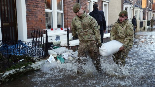 Hundreds of key sites in England at risk of floods - members of the armed forces helping distribute sandbags to residents following flooding in Carlisle