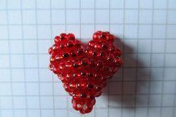 Fädeln Sie aus Perlen ein Herz.