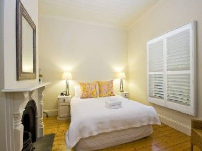 This bedroom exudes old style charm with a beautiful fireplace. Off set with stylish linen in vintage fabric.