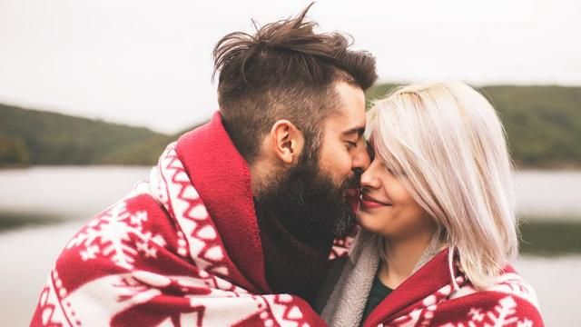 couple cuddling wrapped in a blanket