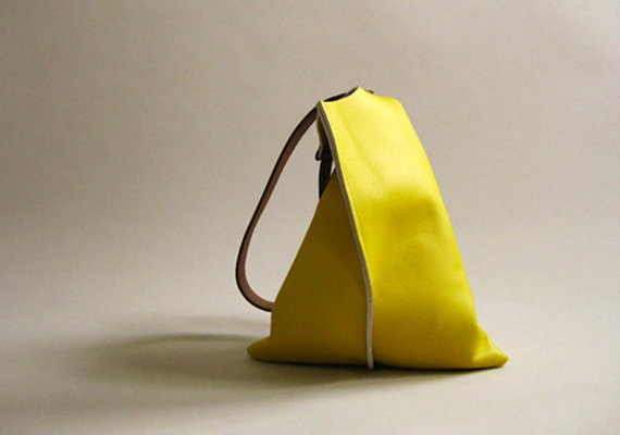 Available in two sizes, this sleek, unlined shoulder bag is crafted from thick, firm, smooth lemon yellow leather with medium length brown leather straps. The bag is finished with double screws and an interior keyring.  From Fog + Foundry. $165