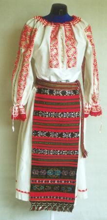 Romanian Women's costume from Maieru, Rodna valley, Bistriţa-Năsăud  Gathered neck linen blouse (cămaşă încreţită), with gathered cuffs with small frill. It is decorated with red and wide gold thread  embroidered motifs making a rectangular strip across the top of the shoulder (altiţă), and vertical stripes (râuri) on the front, and sleeves. The neck has an edging in crochet red wool, and a row of red wool crochet lace is attached to the cuff frills.