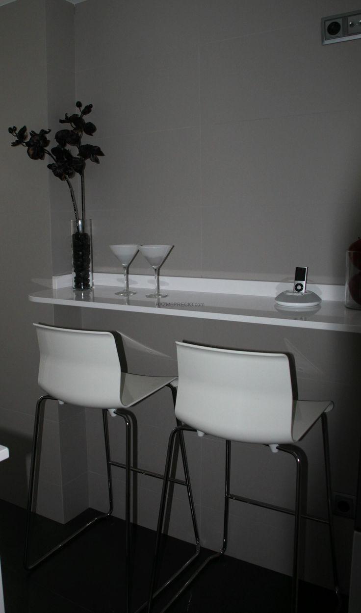 Cocina Luminosa en Madrid: Barra de desayuno: La barra de desayuno realizada en Corian se destaca sutilmente sobre el alicatado porcelánico gris perla