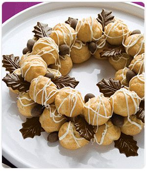 Arrange 24 mini puffs in a wreath shape on serving platter (10 puffs in inner ring and 14 puffs in outer ring). Drizzle puffs generously with white chocolate. Arrange remaining 12 puffs over top of ring. Drizzle with additional white chocolate. Decorate and serve. Garnish Ideas DCD Chocolate Leaves, DCD Chocolate and Cinnamon Dusted Almonds