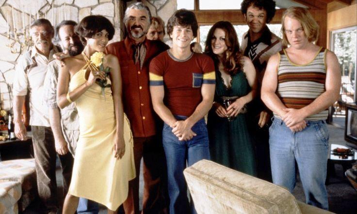 """Boogie Nights"" promo still, 1997.  L to R: Jack Wallace, Ricky Jay, Nicole Ari Parker, Burt Reynolds, William H. Macy, Mark Wahlberg, Julianne Moore, John C. Reilly, Philip Seymour Hoffman."