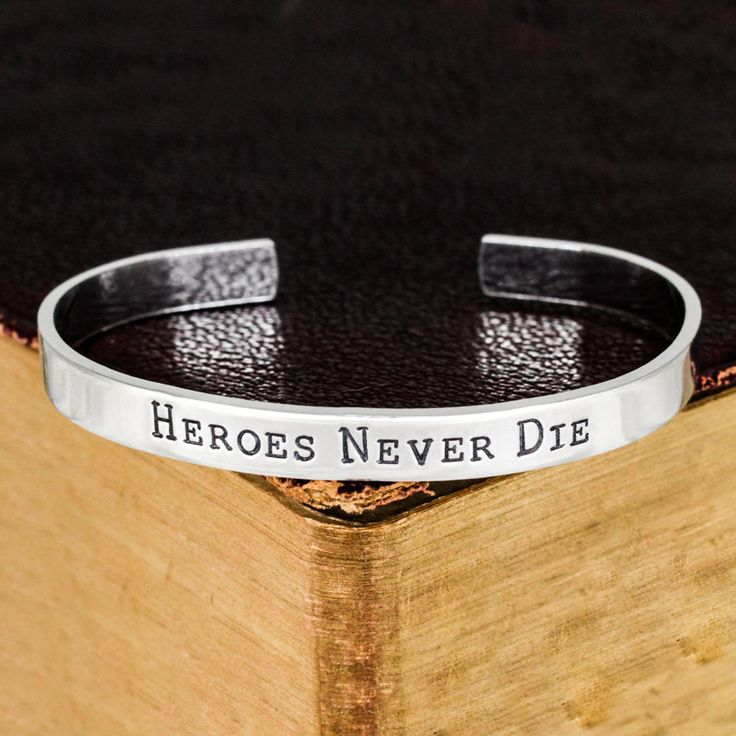"""This """"Heroes Never Die"""" aluminum bracelet is stamped by hand, one letter at a time. This bracelet is made on a 1/4"""" wide aluminum blank and is shaped by hand. Please avoid contact with water to keep t"""