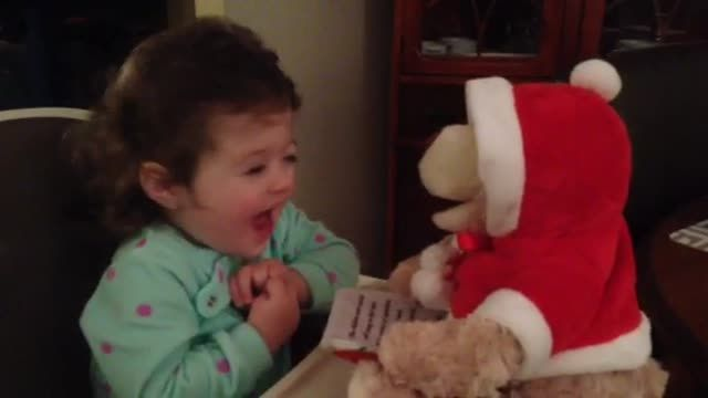 Take a look at the sheer happiness this singing bear brings to an adorable toddler. You can see her eyes light up as the bear reads her a Christmas story. Priceless! Precious toddler charmed by singing teddy bear.