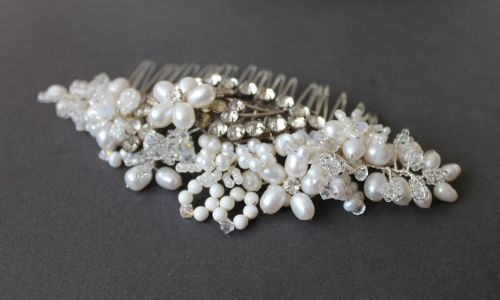 Flora- A stunning one of a kind hair comb created from delicate seed beads, Swarovski crystals and pearls, mother of pearl beads and freshwater pearls all in beautiful ivory tones. The centre of this piece has been created using a 1930's diamanté buckle.