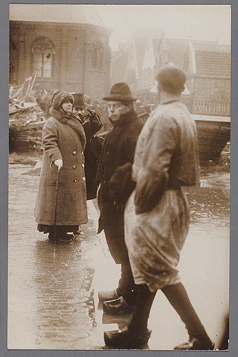 Koningin Wilhelmina in de Kerkbuurt op Marken. De koningin wordt ingelicht door de burgemeester. De man met afgewend hoofd is C. Kes Czn. Op de achtergrond de Ned. Herv. kerk. Watersnood 1916 #NoordHolland #Marken