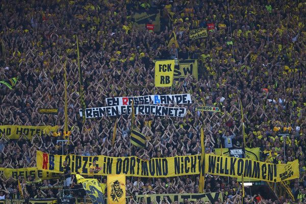 Fans of Borussia Dortmund hold up signs and flags against the club of RB Leipzig during the Bundesliga match between Borussia Dortmund and RB Leipzig at Signal Iduna Park on October 14, 2017 in Dortmund, Germany.