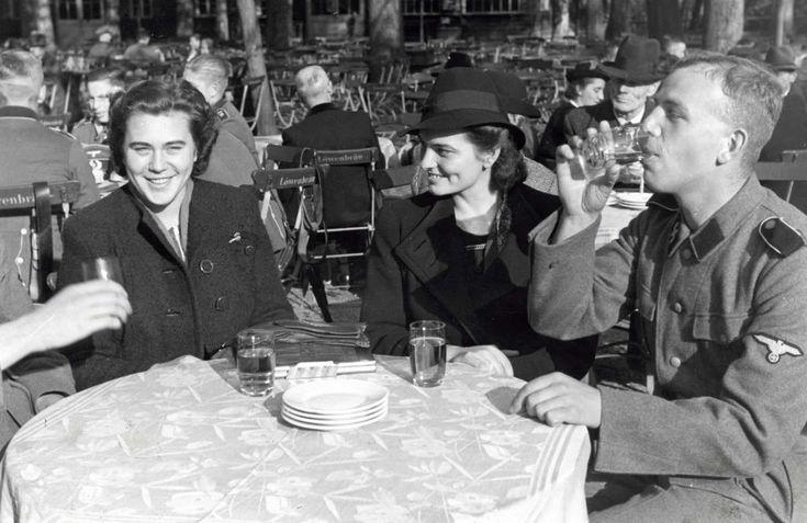 Tweede Wereldoorlog. Nederlandse vrijwilligers.Mannen van het SS-regiment Westland in München aan drinkend een tafel op een terras met twee Duitse meisjes / vrouwen. Duitsland, München, 1941.