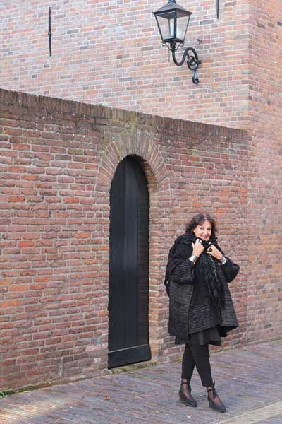 Christhilde draagt een jas van Annette Görtz, gaat meestal gekleed in zwart. Draagt nu als accent een kleurrijke shawl van Kenzo. Schoenen: Jan Jansen Wat sieraden betreft maakt ze iedere dag een keuze uit haar uitgebreide etnische verzameling. De zwarte ring heeft ze overigens gekocht op de Biennale in Venetië.