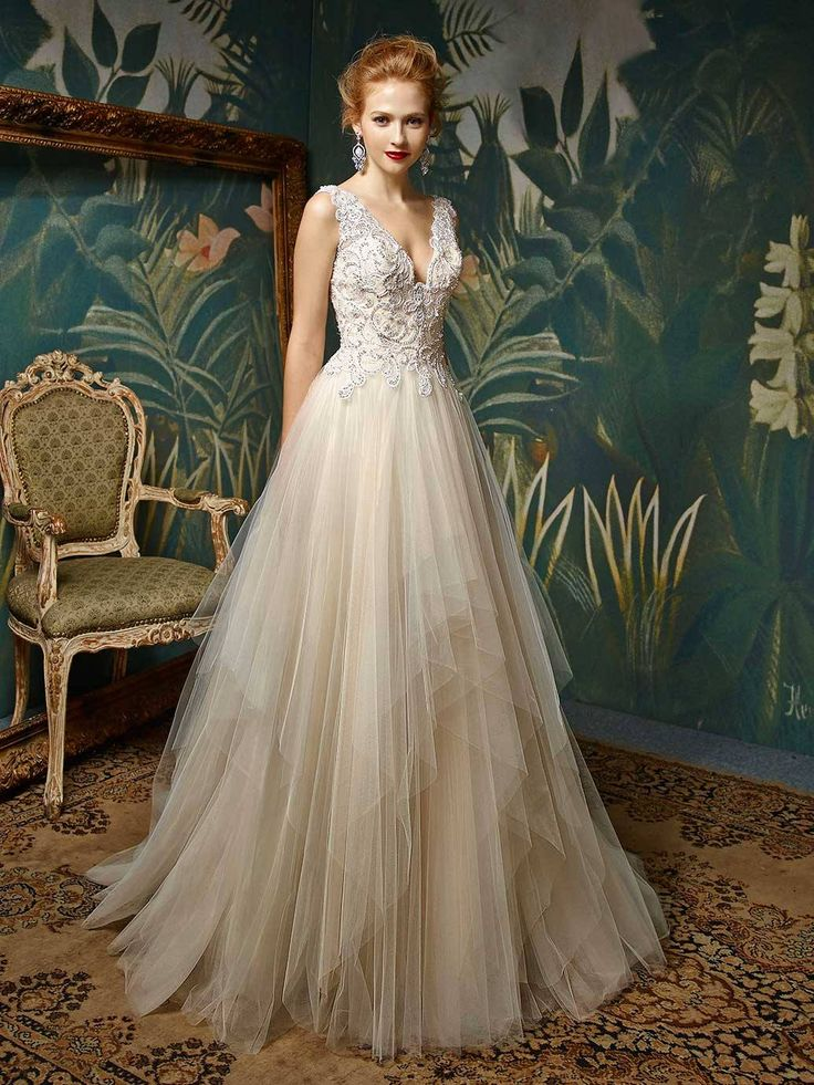 Josetta, from the new Enzoani Blue 2017  For the bride looking for a romantic and dreamy fairytale gown, this full-length, sleeveless A-line gown hits all the right notes. A plunging V-neckline and low V-back on the beaded embroidered lace bodice add sultriness while the single layer tulle skirt creates the sweetest look. Complete with an invisible back zipper. Our sample is in a size 14 in Ivory/Beige but also available in Ivory/