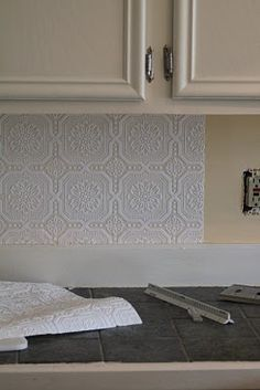 Painted wallpaper on the backsplash mimics the look of pressed tin at a budget-friendly price.