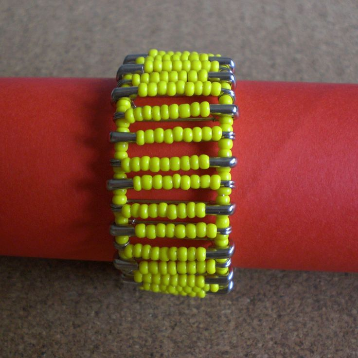 Bracelet made using safety pins with yellow plastic beads. Connected with yellow plastic beads.