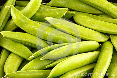 A closeup of whole sugar snap peas in their pods