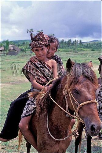 INDONESIA, SAWU (SEBA) ISLAND BOY & GIRL ON HORSE IN TRADITIONAL IKAT COSTUMES