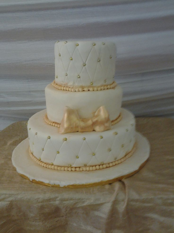 ivory and gold wedding cake with a bow