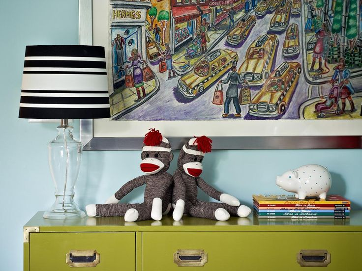 Create a colorful, creative space for your child with this light blue transitional kids room. A lime green dresser, colorful artwork and a black and white striped lamp brighten up the space, while a pair of sock monkeys and pile of books personalize the space.