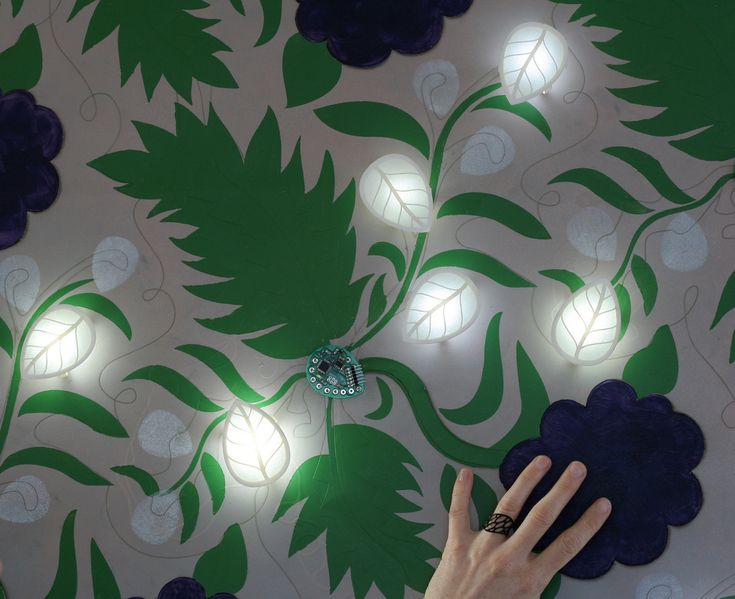Super cool! Lilly Pad is a washable programable circuit board that can be sewn into fabric with conductive thread. There are led lights, and all kinds of sensors you can use.