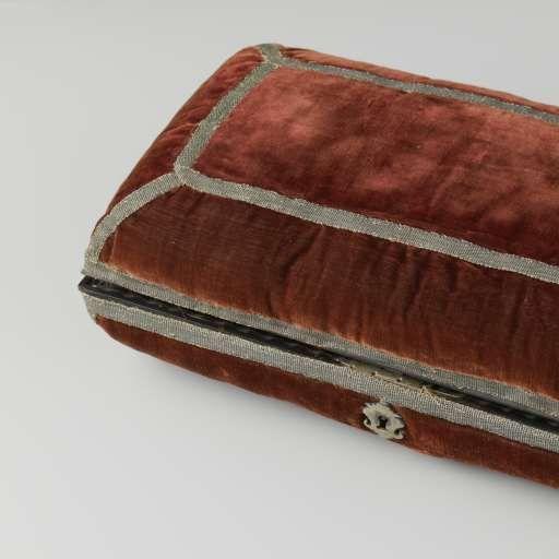 Langwerpig kussen bestaande uit twee gelijke helften, bekleed met rood fluweel versierd met zilveren passement. Binnenwerk van hout belijmd met schildpad en voorzien van compartimenten met beschilderde deksels met rollijsten van ebbenhout. Messing slot mi