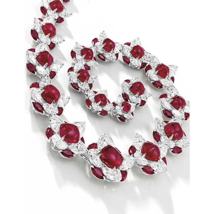FINE RUBY AND DIAMOND NECKLACE AND PAIR OF MATCHING EARRINGS, FAIDEE The necklace set with twenty-two graduated sugar loaf cabochon rubies, each surrounded by eight marquise-shaped diamonds and four marquise-shaped rubies; and pair of earrings en suite; the rubies and diamonds together weighing approximately 124.80 and 59.25 carats respectively, mounted in platinum and 18 karat yellow gold, length approximately 420mm.