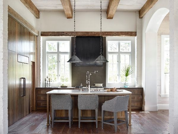 A custom zinc range hood, Calacatta Gold marble countertops, and cypress cabinets lend rustic elegance to the kitchen. Light fixtures wear an aged patina. - Elegant Homes © / Photo: Emily Jenkins Followill / Design: Courtney Dickey