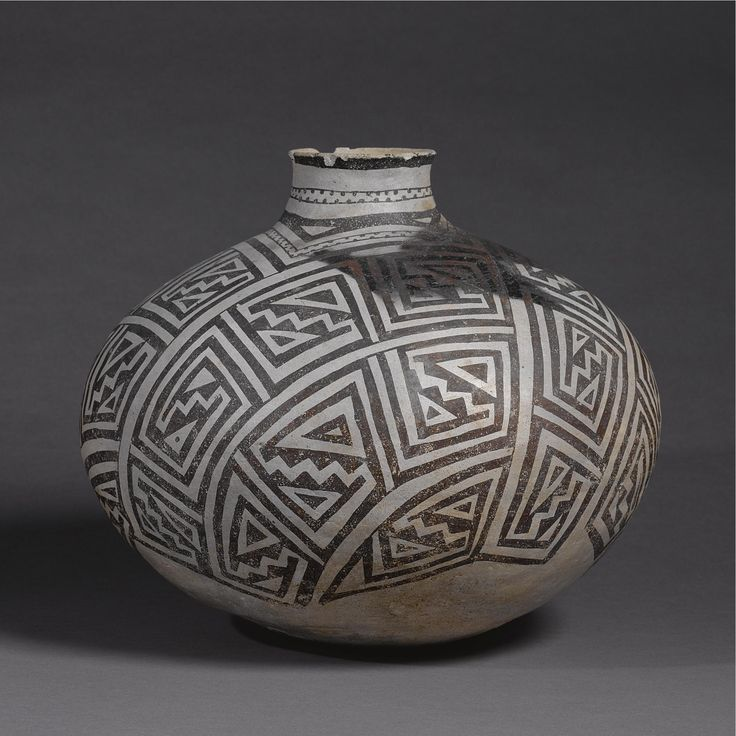 """A Large Socorro Black-On-White Storage Jar circa 1200 A.D., of slightly compressed globular form, painted with a series of arching panels enclosing classic angular and stepped designs, the raised neck decorated with a dotted """"collar"""" beneath a darkened rim. height 12 1/2 in. by diameter 14 3/4 in. Sotheby's. AMERICAN INDIAN ART 18 May 2007. NY."""