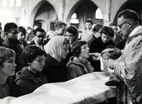 Religies, godsdiensten, rooms-katholicisme. Mensen (met name jongeren) in een rooms-katholieke kerk wachten in de rij om ter communie te gaan. De priester deelt de hosties uit. Plaats en jaartal onbekend [Nederland, omstreeks 1960].