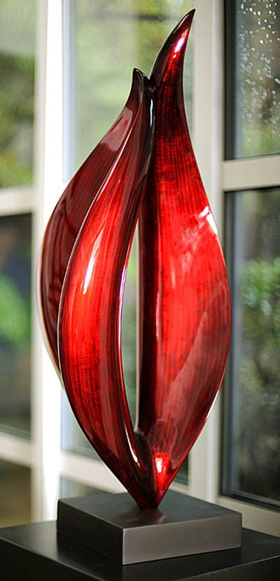 """Flame-Small"" Contemporary Wood Sculpture, Stohans Showcase. Vivid red modern wood sculpture depicting an abstract flame consisting of two vertical forms converging with points on the tops and an open center area between them. The Flame sculpture has a bright red base color with subdued black vertical stripes and has been mounted on a square black lacquered wood base."