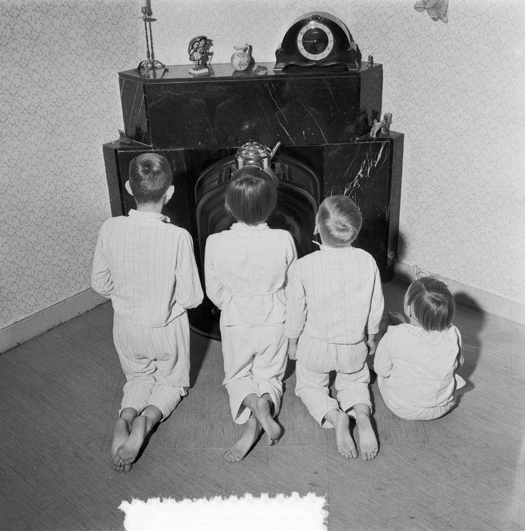 De kinderen zingen Sinterklaasliedjes bij de kolenkachel.