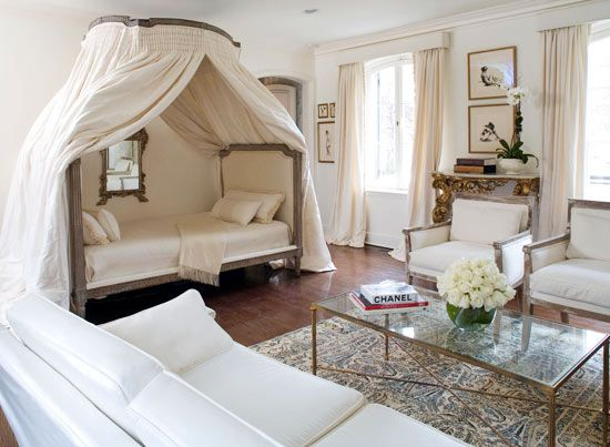 Modern & Luxurious Bedroom With an 18th-century canopy bed as its centerpiece, this bedroom exudes modern luxury. Designer Gail Plechaty enhanced the symmetry of the space by creating a sitting area, continuing the monochromatic off-white scheme for a look of natural comfort. A 19th-century Florentine rococo table gilded in 24-carat gold and topped with Carrara marble adds to the luxurious air.