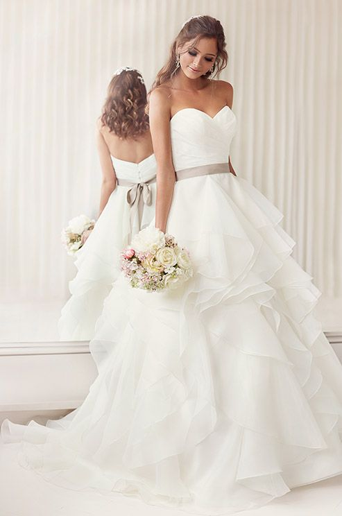 This wedding dress features a figure-flattering asymmetrical ruched bodice, and soft, billowing layers of organza. Essense of Australia, Fall 2014