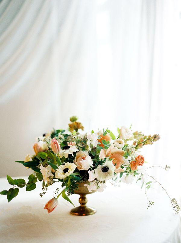 stunning centerpiece by Saipua featuring ranunculus, tulips, tuberose, anemones, sweet peas and garden roses