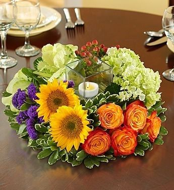 A festive garden #centerpiece of sunflowers, hydrangea and garden roses surrounding a votive candle in a chic glass cube.