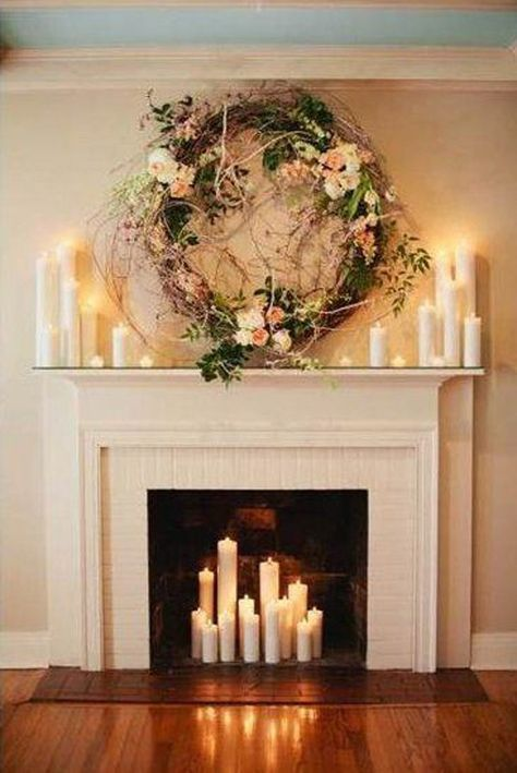 Fireplace with lots of candles and a large floral wreath.
