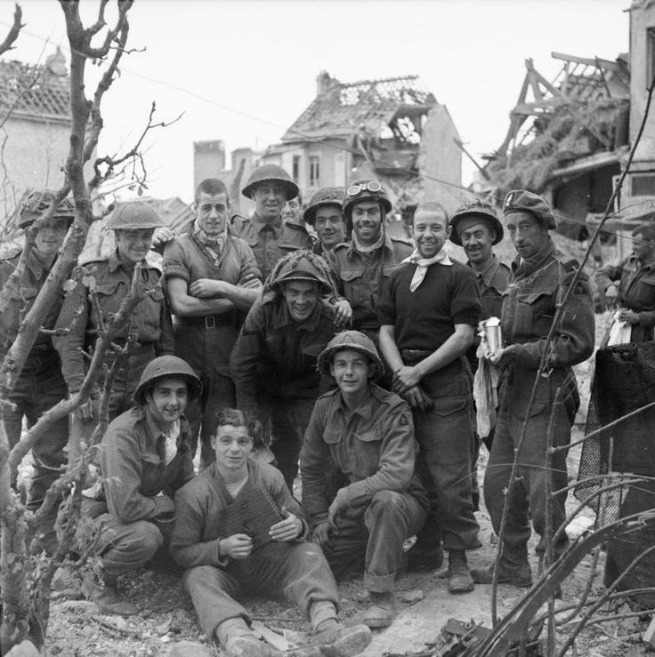 A cheerful group of soldiers from 3rd Division pose for a photograph in Caen, 10 July 1944