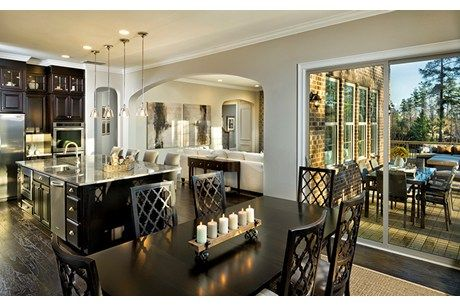 A stunning kitchen and great room open to a gorgeous outdoor  space. The Monterey plan, built by Standard Pacific Homes at Bear Creek At Palisades. Charlotte, NC.