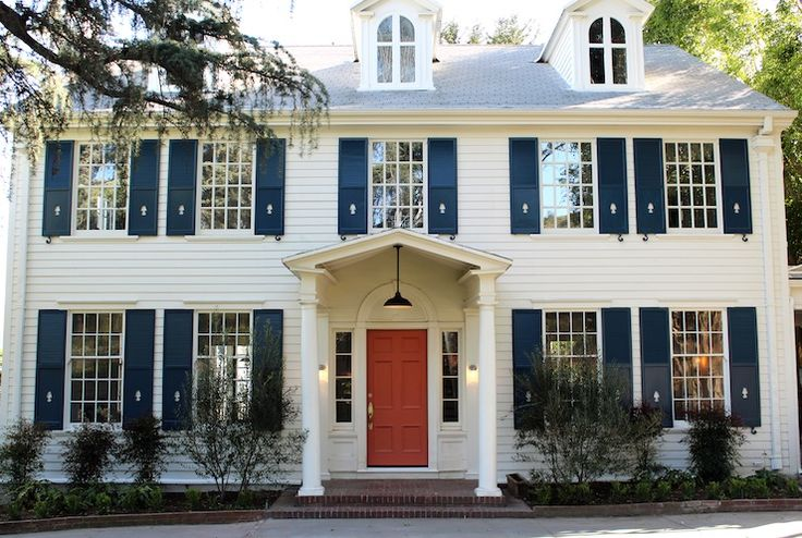 Kishani Perera - home exteriors - Benjamin Moore - Golden Gate - colonial home, navy blue shutters, in the midnight hour, painted coral front door,