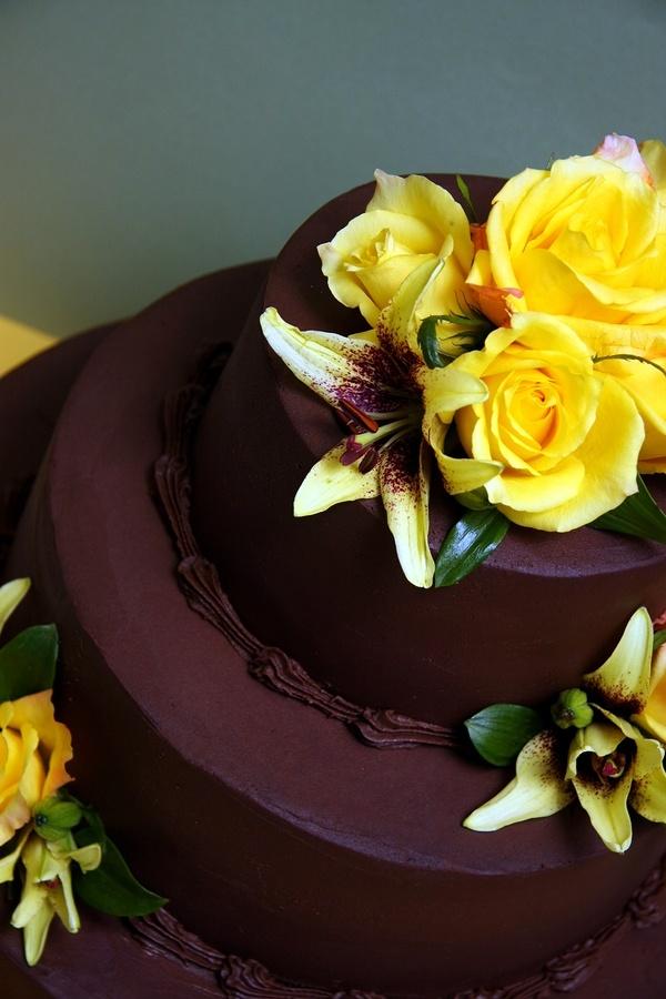 Chokolade lagkage i tre lag med gule roser og liljer