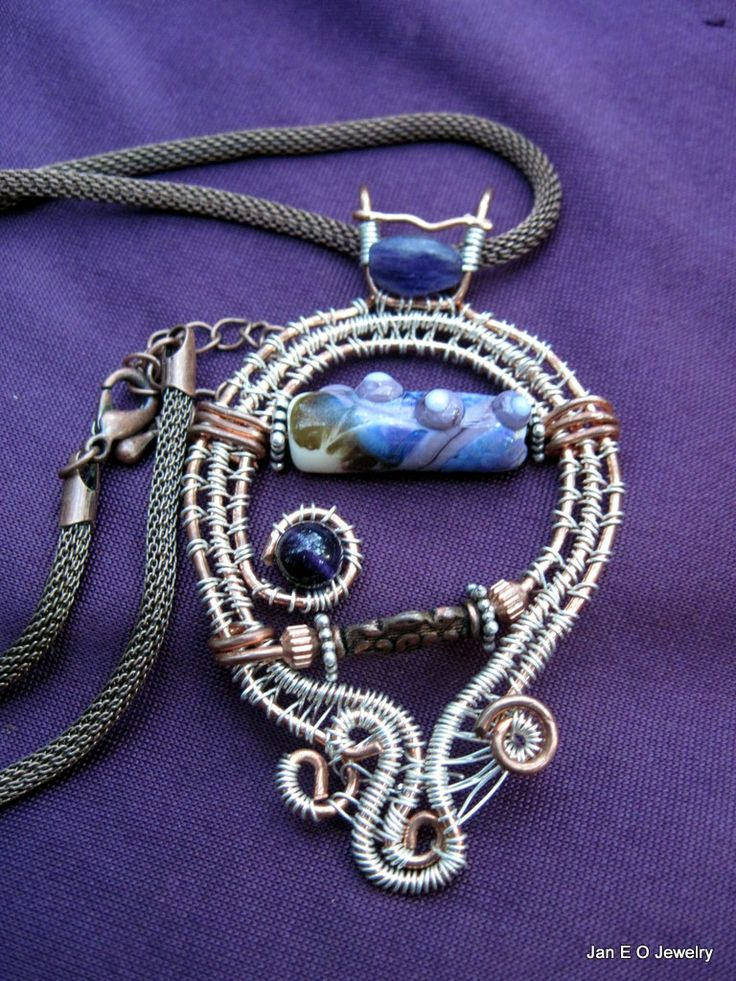 Freeform wireweave pendant showcases a purple lampwork bead and amethyst.  The pendant has a copper inner wire and is wire wrapped with silver copper core wire.  The lampwork bead is one of a kind and was designed by a friend.  The pendant is three inches long and about and inch and a half at the widest point.    The pendant hangs from an 18 inch copper chain with a two inch extension chain.