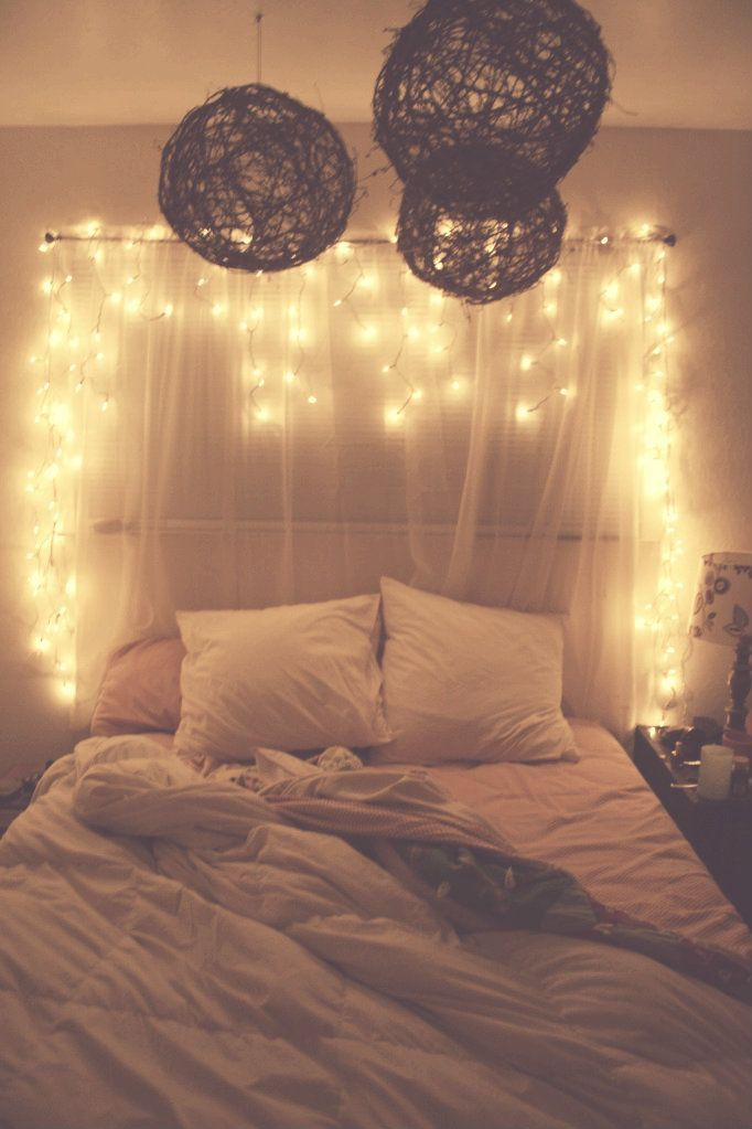 Lights and sheer curtains behind bed