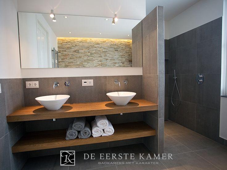 Mooie combinatie van grijze tegels, hout, stucwerk en een grote spiegel.
