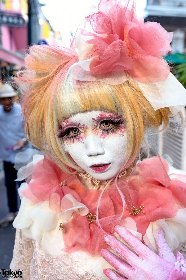 Japanese shironuri artist Minori is someone who is very hard to miss when she's walking around the streets of Harajuku. This time, she was wearing a handmade and vintage outfit that features a pink chiffon headpiece, a pink chiffon flowers collar on a lace dress, tights hand painted with pink flowers, and hand painted wedges with chiffon tied at the ankles. Her bag in vintage and she's also decorated her dress with tassels. (Tokyo Fashion, 2014)