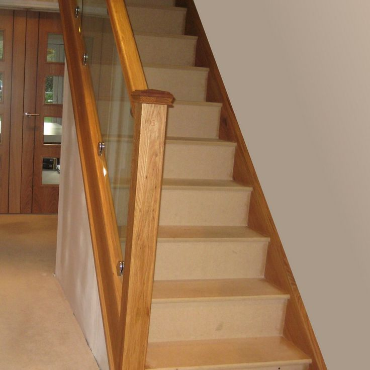 American white oak staircase with toughened, polished glass balustrade fixed using chrome clamps.