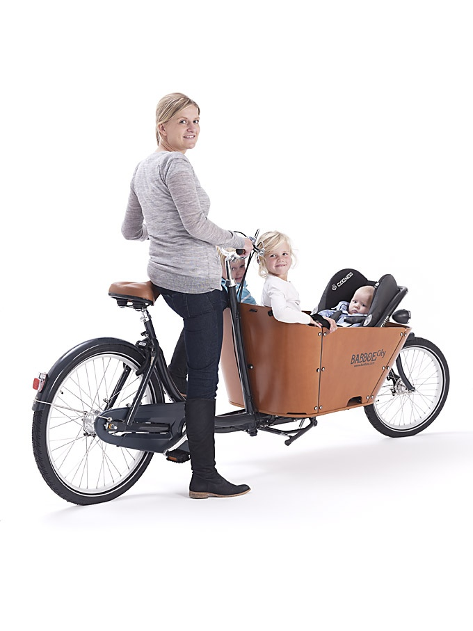 The Babboe City is a robust 2-wheel cargo bike with an attractive design. The striking beech wood container has smooth, curved corners and a high edge for added safety. The tyres are extra thick, making the cargo bike even more comfortable. The colour combination of anthracite grey/cognac together with the cool varnished wooden container gives the Babboe City cargo bike a contemporary and chic look. Mom on the Babboe CIty